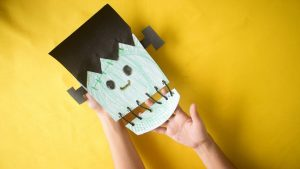 """This project will turn an ordinary paper plate into a confronting Frankenstein face, complete with a stitched up jaw and neck bolts. There is a lot of coloring in with this Halloween craft idea, which you can substitute for painting if you want a different kind of activity. There is also some threading of yarn that will be a bit more challenging for a younger toddler, but will help develop those motor skills if given some time. Full written instructions are included in this post, along with pictures for each step and a video demonstration. [toc] Prepare Your Paper Plate Craft Materials If you want to stick with coloring in rather than painting then your craft materials will be very simple, and mostly mess free. Again, feel free to interchange your crayons for paint. This will require a bit more time when you factor in time to dry and cleaning up the paint brushes and table covering. Paper Plate Frankenstein Video Demonstration Check out the time-lapse video below of the project being completed from start to finish. After you see how the project comes together it will be much easier to do with your kids as you work through the written instructions. [mv_create key=""""18"""" type=""""diy"""" title=""""How to Make a Frankenstein Paper Plate Craft"""" thumbnail=""""https://katherinerosman.com/wp-content/uploads/How-to-Make-a-Frankenstein-from-a-Paper-Plate.jpg""""] Why Make a Frankenstein Face Craft While there is not a lot of educational benefit in Frankenstein's monster, it will certainly get them into the Halloween spirit. This legendary character is more than 200 years old and is a permanent fixture when Halloween decorations go up, and trick or treat costumes are decided. It is easy to create this project and while he has some scary features it is a fun decoration to place around the house. Plus there is always a benefit to creating something from ordinary items like a paper plate. For More Halloween Craft Ideas Check out all of our Halloween craft projects suitable for toddlers here. Eac"""